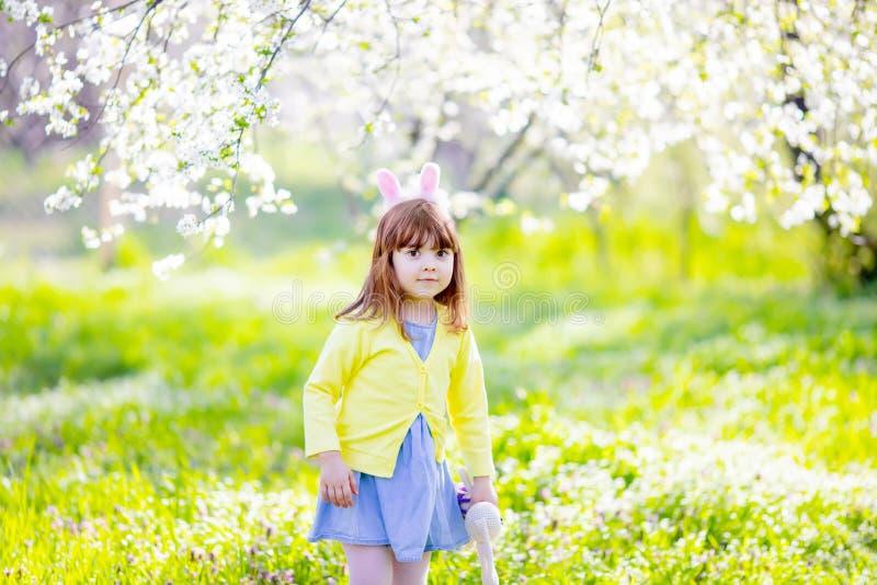 Urocza mała dziewczynka bawić się w kwitnącym jabłoń ogródzie na Wielkanocnego jajka polowaniu Dziecko w wiosna owocowym s zdjęcie royalty free