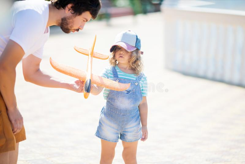 Urocza mała dziewczynka bawić się z pomarańcze zabawki samolotem z jej ojcem fotografia stock