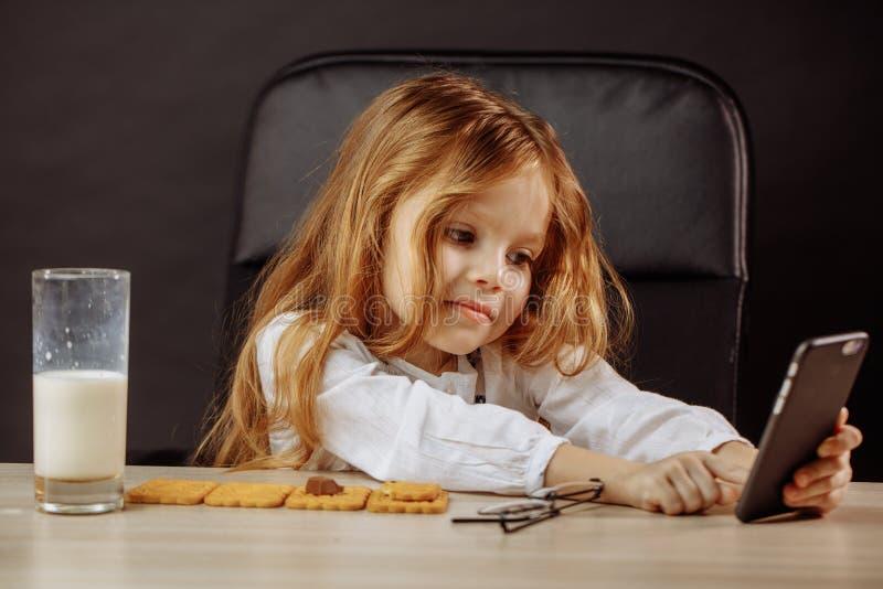 Urocza mała dziewczynka bawić się z smartphone w ojczulka s biurze obraz royalty free