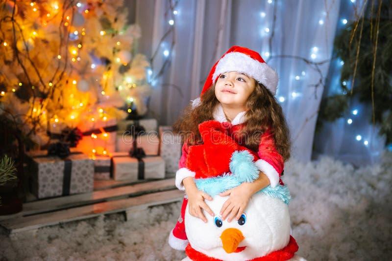 Urocza mała dziewczynka buduje bałwanu w pięknym zima parku Śliczny dziecko bawić się w śniegu Zim aktywność dla obraz stock