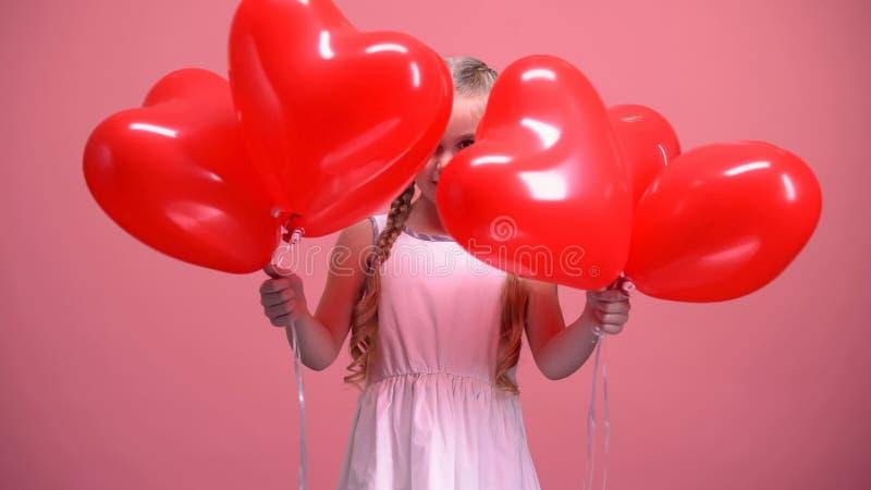 Urocza mała dziewczynka chuje za sercowatą balon walentynek dnia niespodzianką obraz royalty free