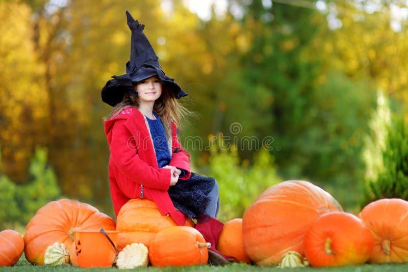Urocza mała dziewczynka jest ubranym Halloween kostium ma zabawę na dyniowej łacie zdjęcia stock