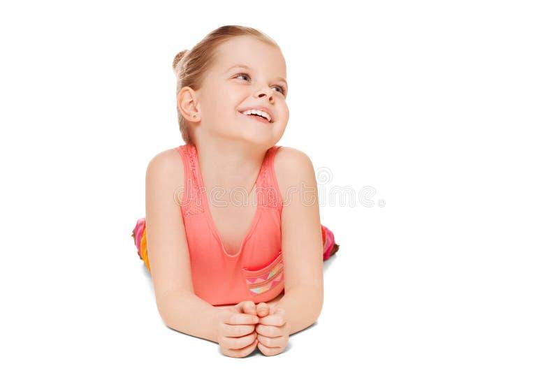 Urocza mała dziewczynka ma zabawy ono uśmiecha się kłama patrzeć strona, odosobniona na białym tle obrazy royalty free