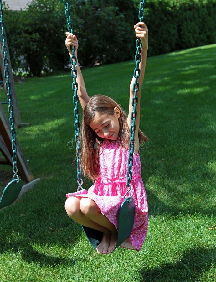 Urocza mała dziewczynka przy huśtawkami w parku z menchiami ubiera podczas lata w Michigan fotografia royalty free