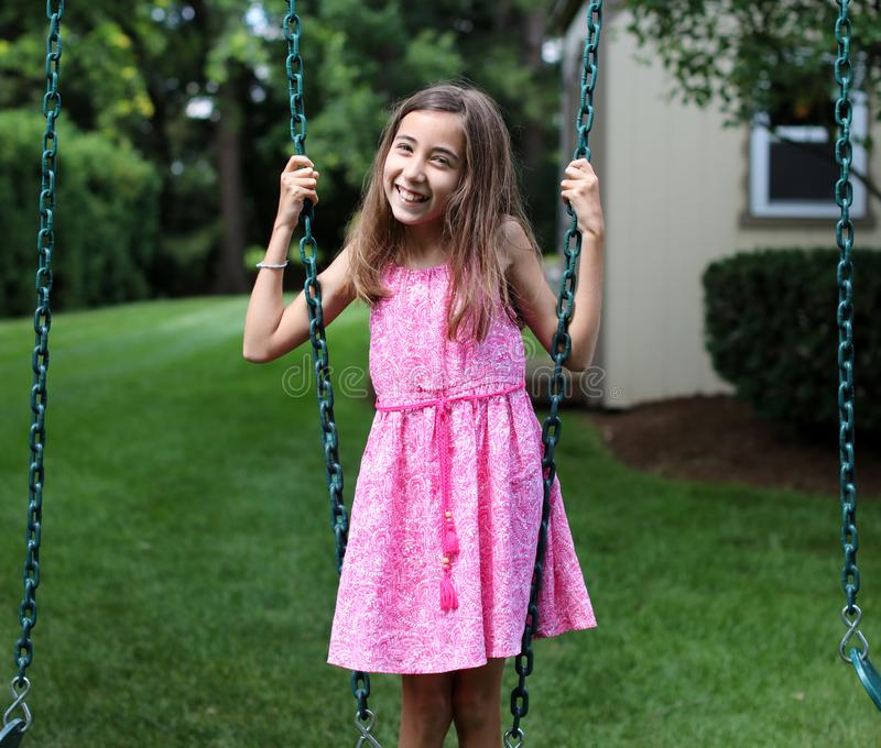 Urocza mała dziewczynka przy huśtawkami w parku z menchiami ubiera podczas lata w Michigan zdjęcia royalty free