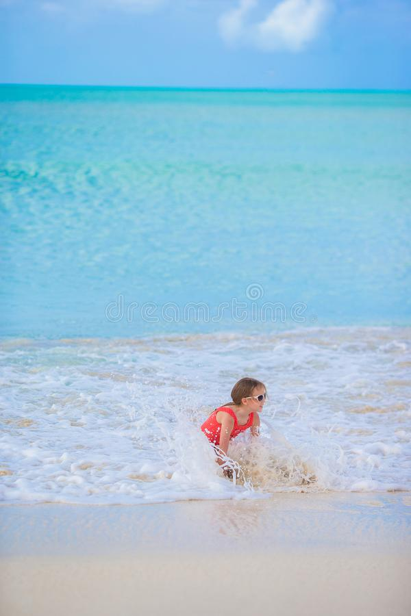 Urocza mała dziewczynka przy plażą ma mnóstwo zabawę w płytkiej wodzie zdjęcia royalty free