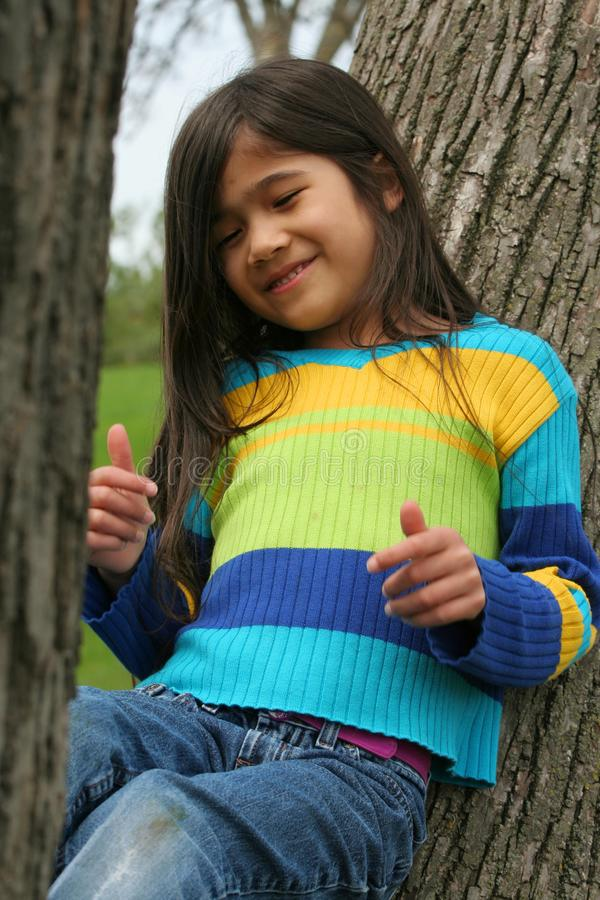 Urocza mała dziewczynka siedzi up przeciw drzewu obraz royalty free