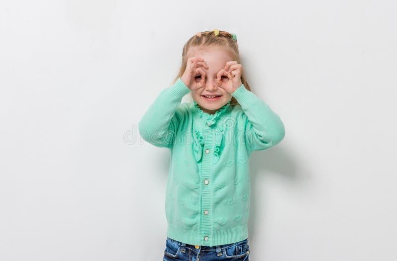 Urocza mała dziewczynka symuluje szkła z jej rękami fotografia royalty free
