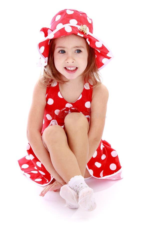 Urocza mała dziewczynka w czerwonym kapeluszu z i sukni fotografia stock