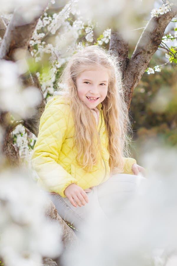 Urocza mała dziewczynka w kwitnąć czereśniowego drzewa ogród obrazy royalty free