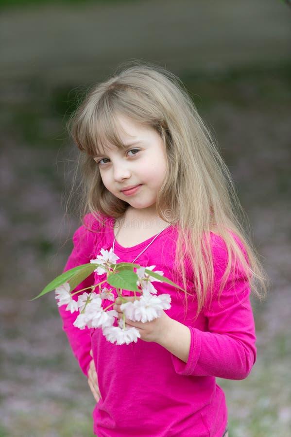 Urocza mała dziewczynka w kwitnącym wiśnia ogródzie obrazy royalty free