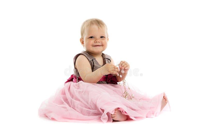 Urocza mała dziewczynka w menchiach ubiera obsiadanie na podłoga obrazy stock