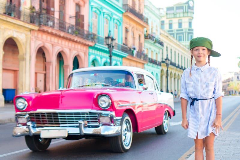 Urocza mała dziewczynka w popularnym terenie w Stary Hawańskim, Kuba Portret dzieciaka tła rocznika klasyczny amerykański samochó zdjęcia royalty free