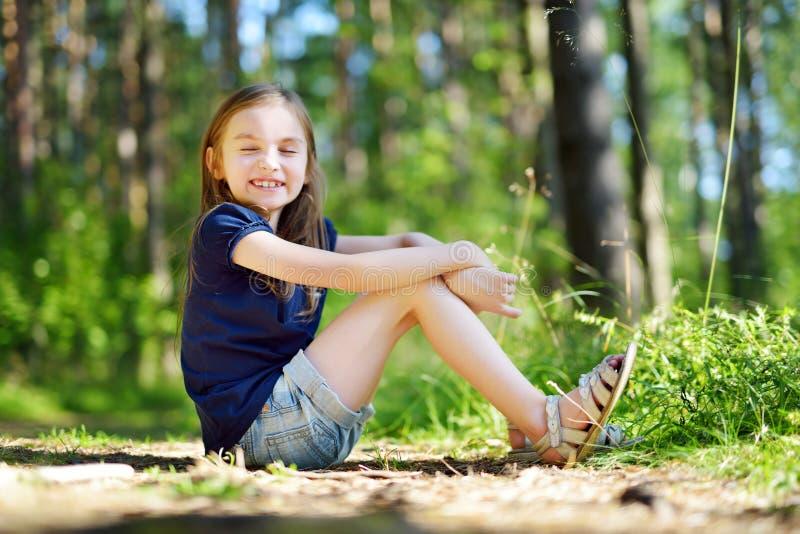 Urocza mała dziewczynka wycieczkuje w lesie na letnim dniu fotografia royalty free