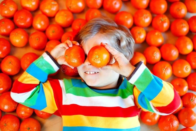 Urocza małe dziecko chłopiec z mandarynek pomarańcz tłem Szczęśliwy uśmiechnięty dziecko ma zabawę z udziałem owoc Zdrowy fotografia royalty free