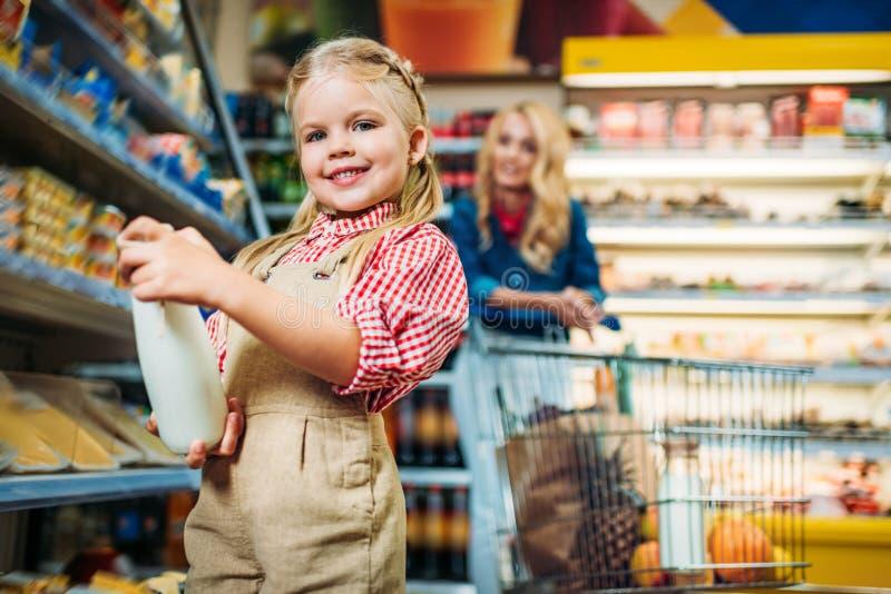urocza małej dziewczynki mienia butelka mleko podczas gdy macierzysta pozycja behind fotografia stock