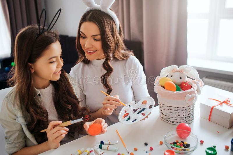 Urocza matka i córka przygotowywamy dla wielkanocy Malują jajka w pokoju Dziewczyna chwyta muśnięcie Macierzysty punkt na pallete zdjęcia royalty free