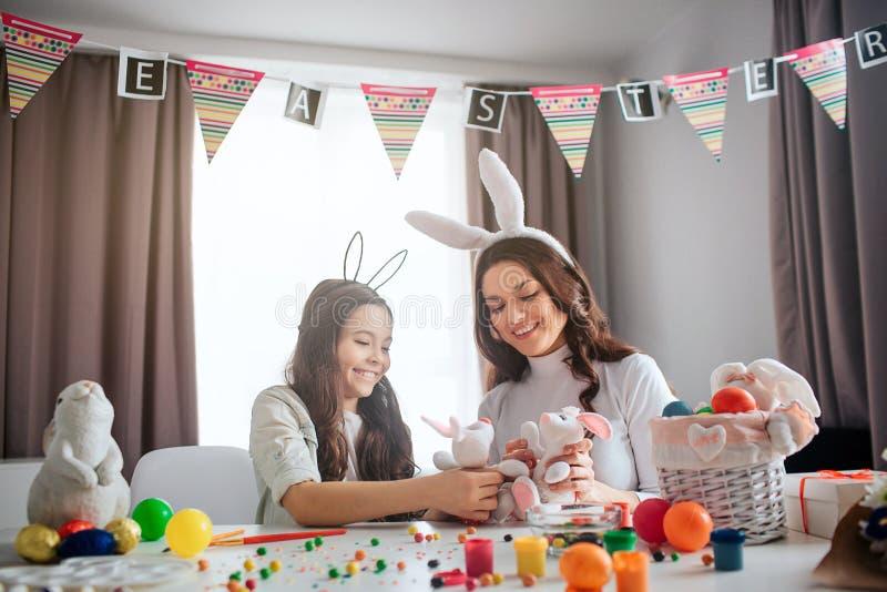 Urocza matka i dziewczyna przygotowywamy dla wielkanocy Bawić się wraz z białymi królik zabawkami na stole Rodzina zabawę wpólnie fotografia royalty free