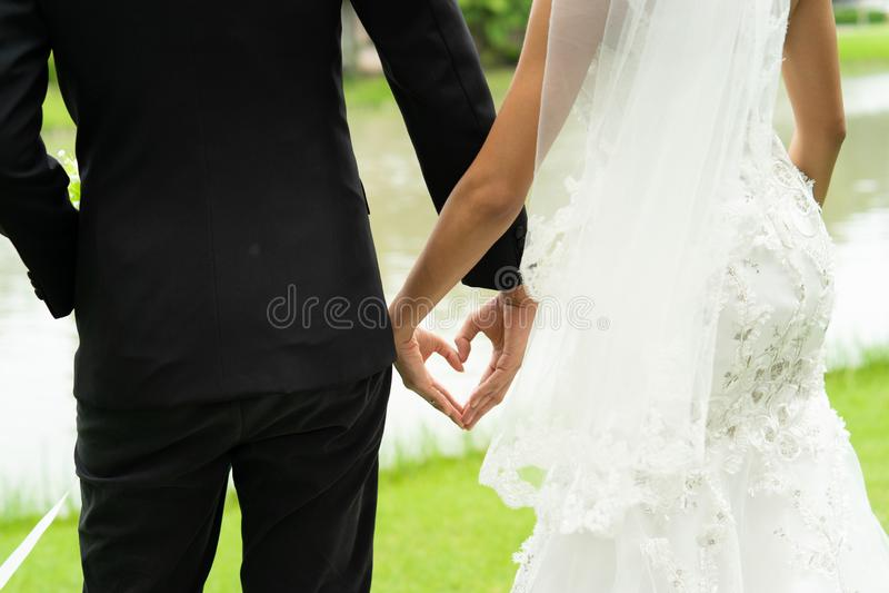 Urocza państwo młodzi chwyta ręka w kierowym kształcie, pary poślubia z miłością na zawsze fotografia royalty free
