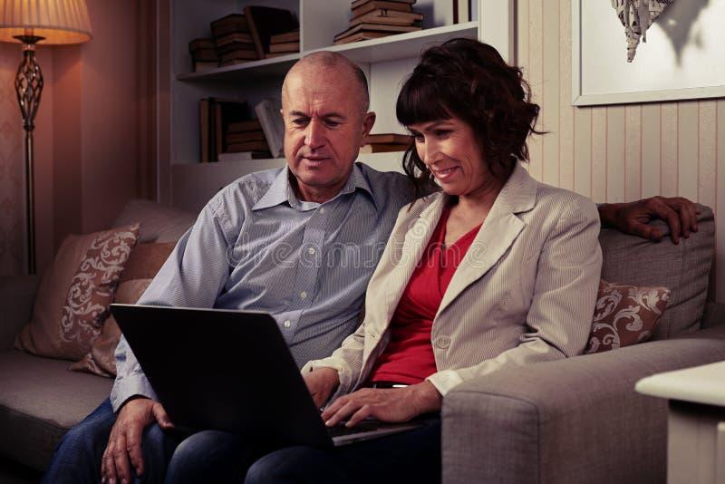 Urocza para bawić się na laptopie w pokoju zdjęcia stock
