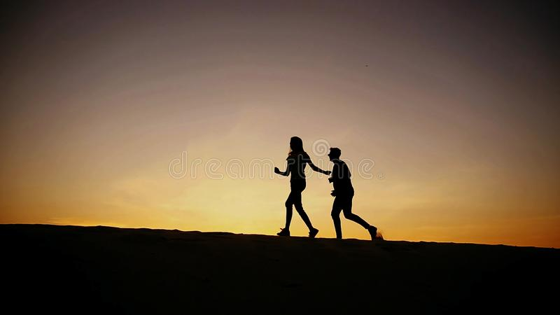 Urocza samiec i kobieta wpólnie biegamy wzdłuż piasek diun i radujemy się obrazy stock
