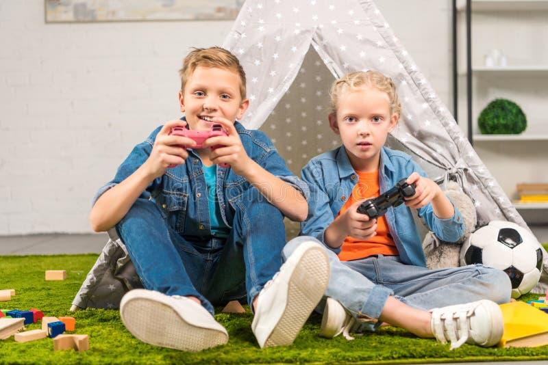 urocza siostra i brat bawić się z joystickami zbliżamy wigwam obrazy stock