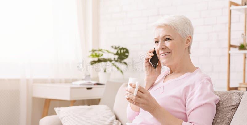Urocza starsza dama ma zabawy rozmowę z jej przyjacielem fotografia stock