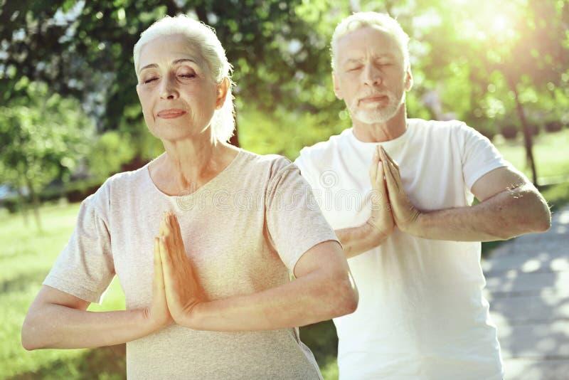 Urocza starzejąca się para medytuje wpólnie zdjęcia royalty free