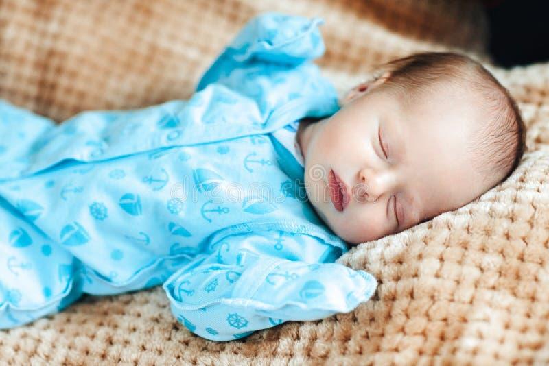 Urocza sypialna nowonarodzona chłopiec ubiera w błękitnych kombinezonach fotografia royalty free