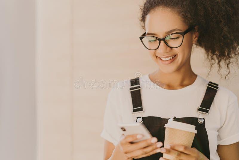 Urocza teeange dziewczyna z kędzierzawym włosy, czek wiadomości karma, wiadomości w ogólnospołecznych sieciach, używa bezpłatnego obrazy stock