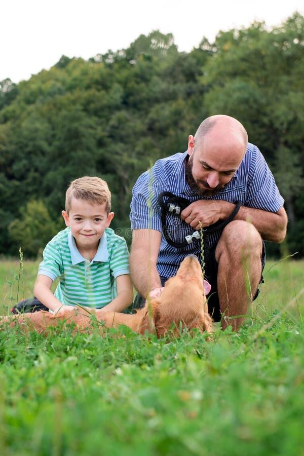 Urocza uśmiechnięta chłopiec z jego modnisia ojcem, bawić się z zwierzę domowe psem obrazy royalty free