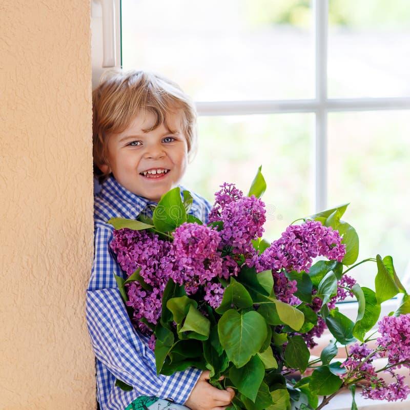 Urocza uśmiechnięta chłopiec z kwitnącym purpurowym bzem kwitnie obraz stock
