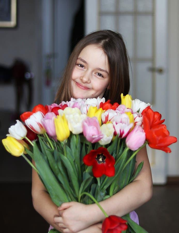Urocza uśmiechnięta mała dziewczynka trzyma dużego bukiet tulipany, salowego zdjęcie royalty free