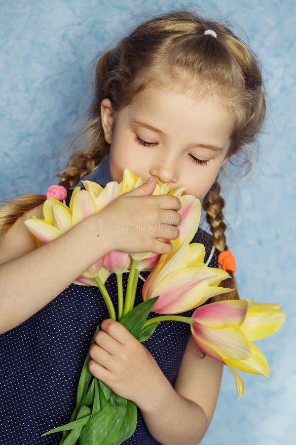 Urocza uśmiechnięta mała dziewczynka z tulipanami obrazy stock