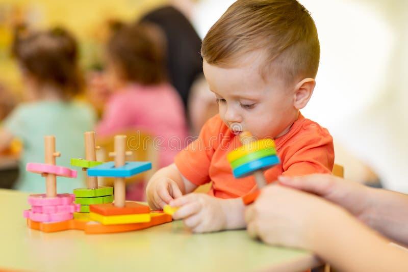 Urocze śliczne chłopiec sztuki z edukacyjną brakarką bawją się przy dziecinem lub pepinierą Zdrowy szczęśliwy berbecia dziecko obraz royalty free
