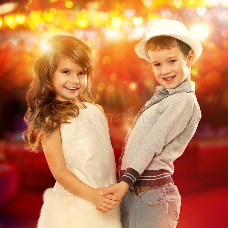 Urocze chłopiec i dziewczyny mienia ręki Dzieciak miłość obraz stock