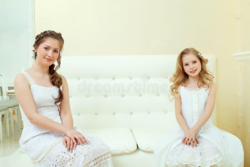 Urocze eleganckie siostry siedzi na białej leżance fotografia royalty free