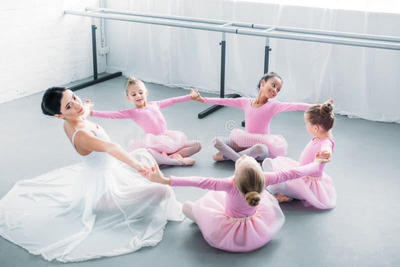 urocze małe baleriny i młody nauczyciel ćwiczy wpólnie obrazy stock