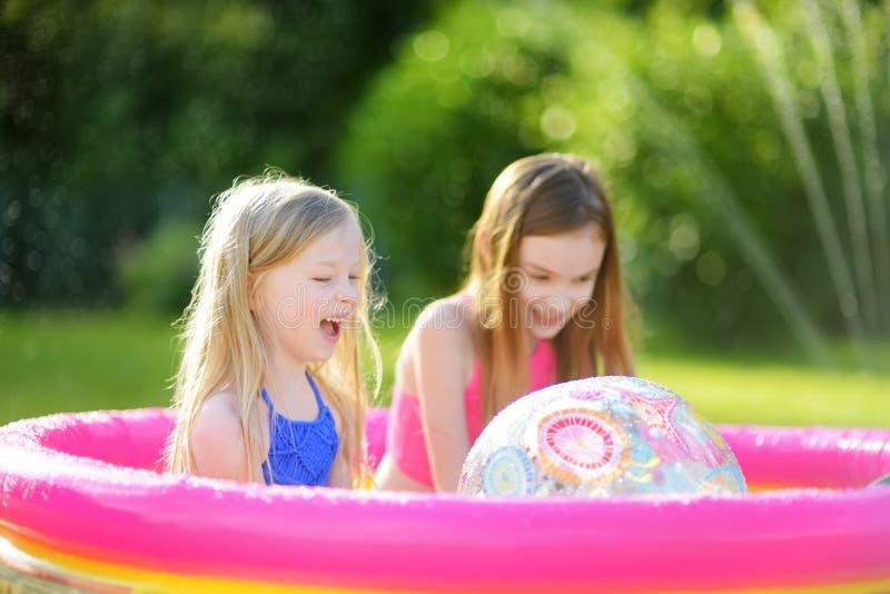 Urocze małe dziewczynki bawić się w nadmuchiwanym dziecko basenie Szczęśliwi dzieciaki bryzga w kolorowej ogrodowej sztuce ześrod fotografia stock