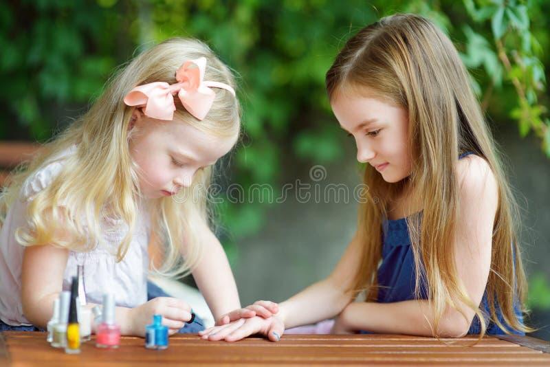 Urocze małe dziewczynki ma zabawę bawić się w domu z kolorowym gwoździa połyskiem robi manicure'owi i maluje gwoździe obrazy royalty free