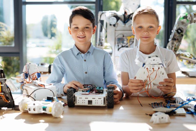 Urocze nastoletnie chłopiec pozuje z ich robotami zdjęcie stock