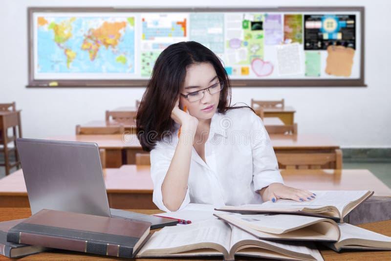 Uroczego żeńskiego ucznia czytelnicze książki w klasie zdjęcie royalty free