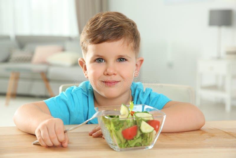 Uroczego chłopiec łasowania jarzynowa sałatka przy stołem fotografia stock