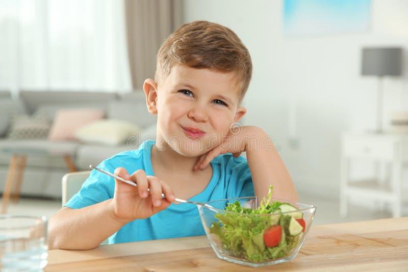 Uroczego chłopiec łasowania jarzynowa sałatka przy stołem obrazy royalty free
