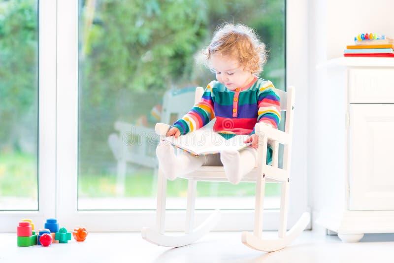 Uroczej berbeć dziewczyny czytelnicza książka w kołysać krzesła zdjęcia royalty free