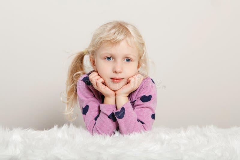 Uroczej białej blondynki Kaukaska preschool dziewczyna siedzi na białym futerkowym dywaniku w różowych purpur ubraniach zdjęcie royalty free