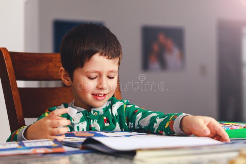 Uroczej chłopiec czytelnicza książka przed iść spać Szczęśliwy ki obraz stock