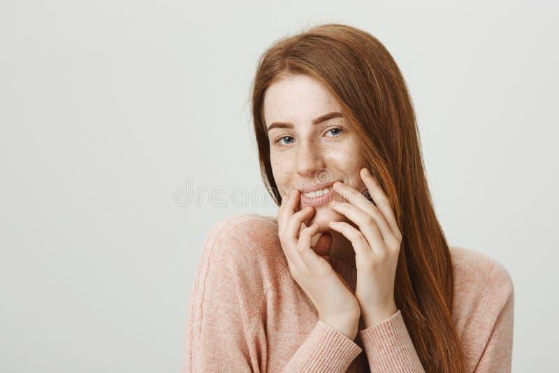 Uroczej i zmysłowej rudzielec europejski żeński być nieśmiały, trzymający wręcza blisko podbródka i ono uśmiecha się seductively  obrazy stock