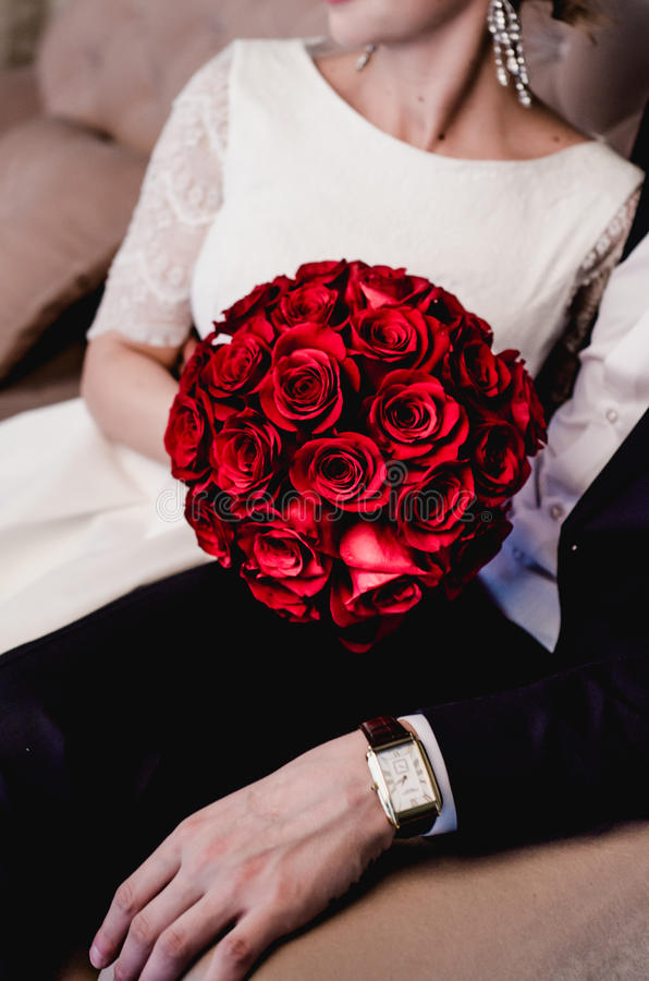 Uroczej pary elegancka panna młoda i elegancki fornal odpoczywa na beżowej kanapie wpólnie Piękny round bukiet czerwonych róż kwi zdjęcie stock