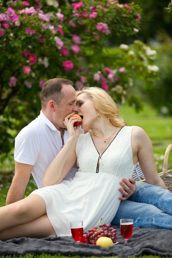 Uroczej pary zjadliwy jabłko na pinkinie obraz stock